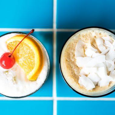 espresso martini and a amaretto sour with orange and a cherry